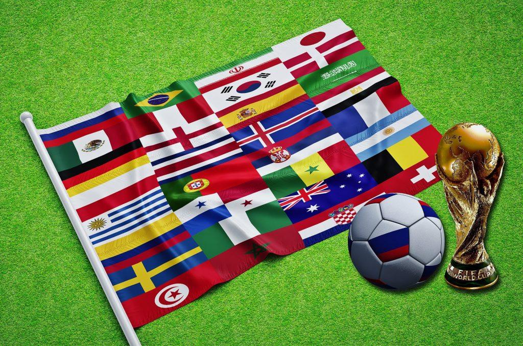 Eine Flagge mit vielen Landesflaggen darauf, neben einem Ball und Pokal